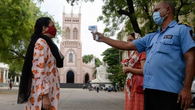 A private security guard checks the temperature of a devotee before mass, in Hyderabad