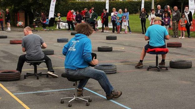 Three men race around a course on office chairs watched by a crowd