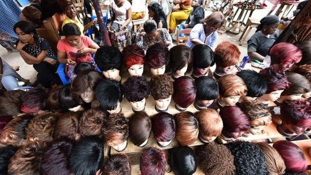 Women make wigs with artificial hair in a wig shop in a market in Abidjan, Ivory Coast