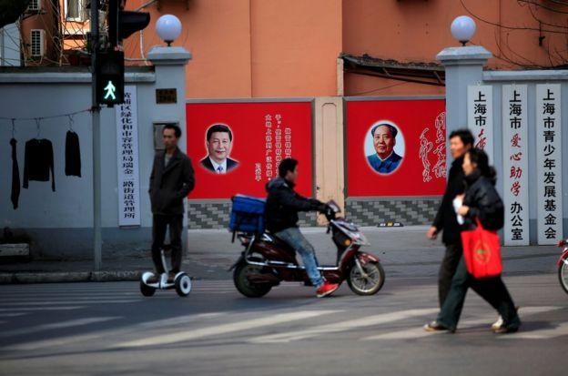 上海街頭行人路過習近平和毛澤東並排的宣傳貼