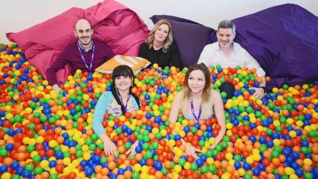 Empleados de Sleeping Giant Media en una piscina de pelotas de colores