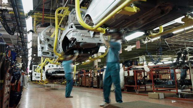 Imagem mostra dois trabalhos no processo de montagem de carros em uma indústria de veículos