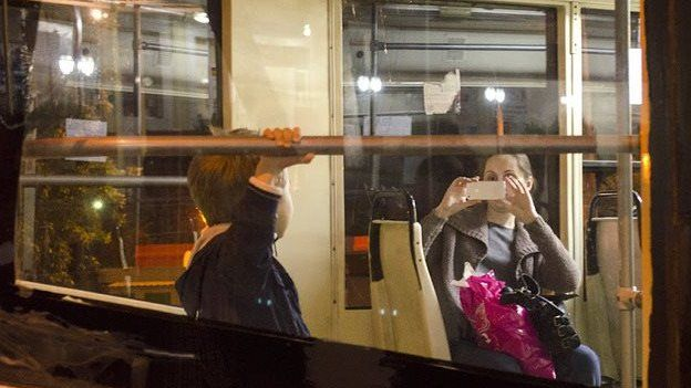 A woman takes a photo of her son riding a tram in Tashkent