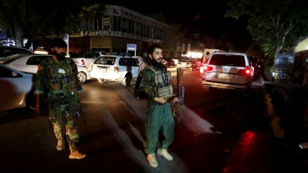 Afghan security officers stands guard outside the emergency hospital in Kabul after a car bomb blast