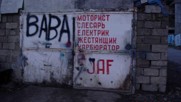 """Надпись красной краской на белых, железных дверях: """"моторист"""", """"слесарь"""" """"Електрик"""", """"жестянщик"""", """"карбюратор"""""""