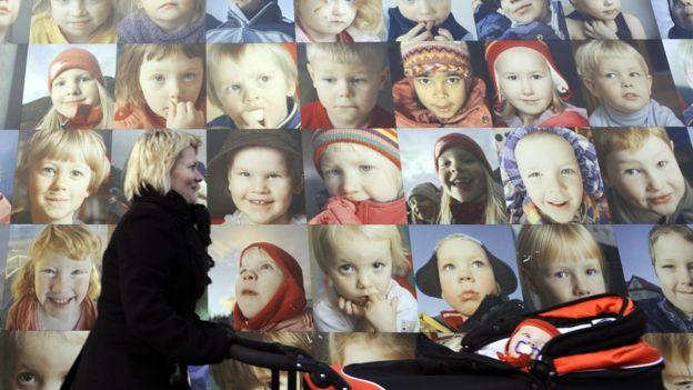 Mulher passa na frente de cartazes com fotos de crianças na Islândia