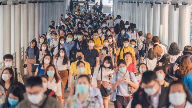 Grupo de personas caminando con mascarilla.