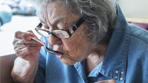 Mujer mayor comiendo.