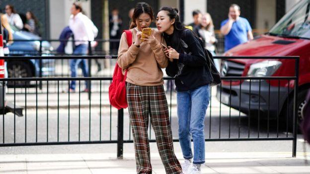 Mujeres viendo celular.