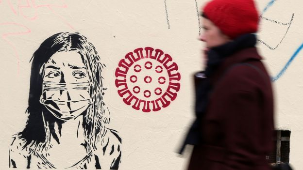 Women walks past graffiti. March 30, 2020, Berlin, Germany