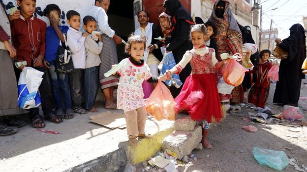 Yemeni children receive free food rations from a charity in Sanaa (14 September 2018)