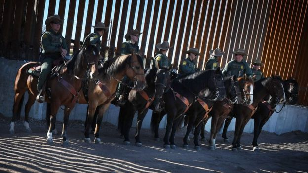 Border Patrol officers at the US border wall