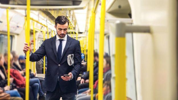 Homem vê o celular no metrô
