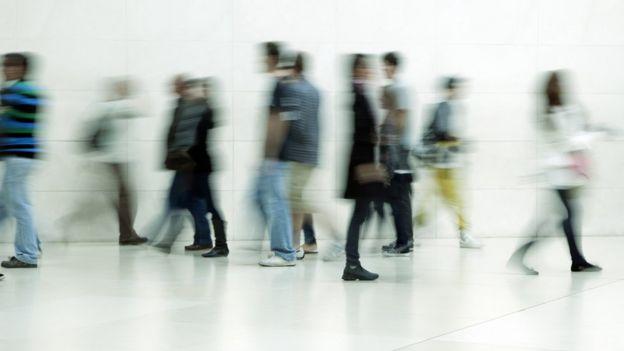 Vultos de pessoas caminhando em frente a corredor branco