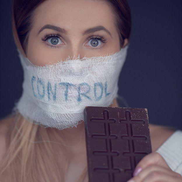 """Mujer con tapabocas que dice """"control"""" y un chocolate en la mano"""