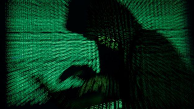 Imagen de una hombre con capucha usando una computadora.