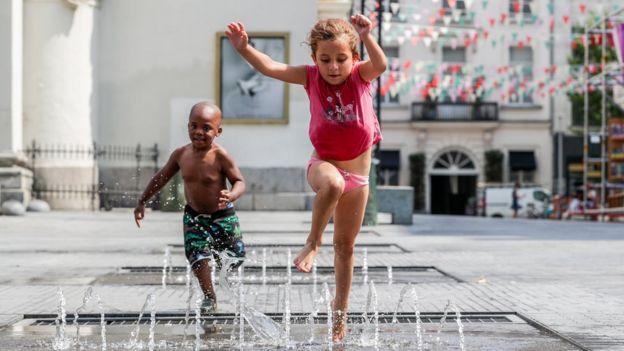 Niños jugando en una fuente