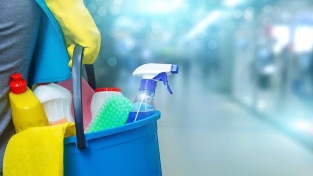 Pessoa carregando produtos de limpeza