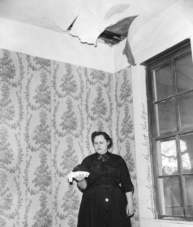 Em foto preto e branca dentro de casa, Ann Elizabeth Hodges segura e olha para meteorito que a atingiu