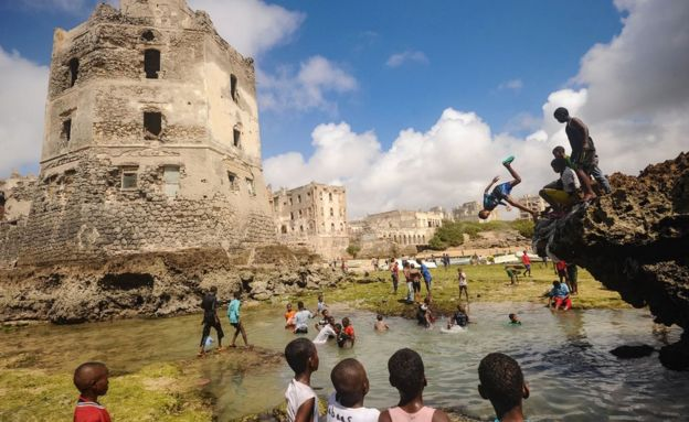 Somali children dive, play and swim in front of the ruins of an old building on the seashore in Mogadishu, Somalia - 2017