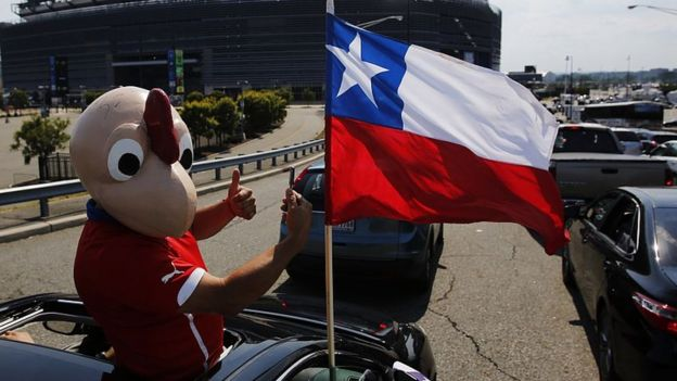 Un hombre vestido en el disfraz de Condorito con la bandera de Chile.