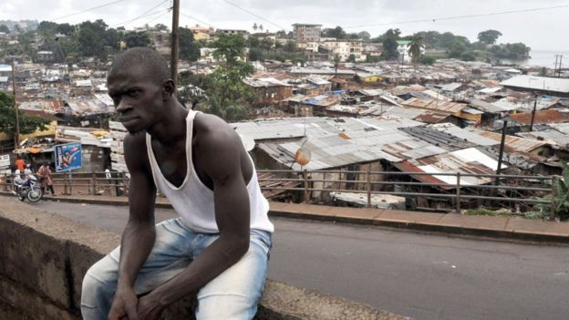 An unidentified man sits on a wall in a township in Freetown on September 20, 2009 where Amnesty International Secretary-General Irene Khan (unseen) is campaigning to fight infant mortality -- one of the highest rates in the world