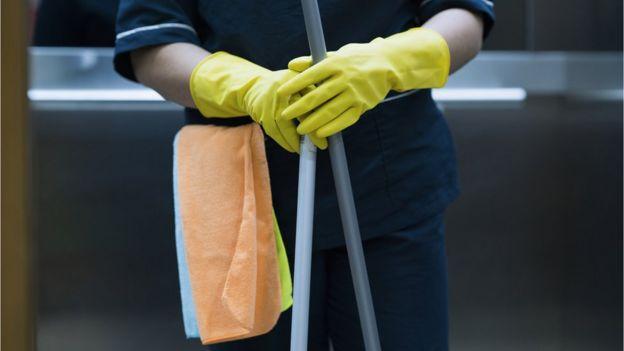 Mujer con guantes amarillos, toallas y una escoba