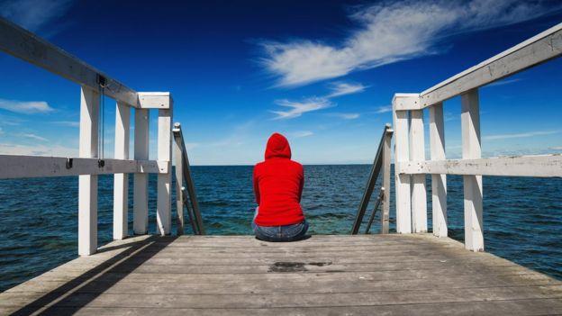Imagen de una chica sentada ante un lago o el mar