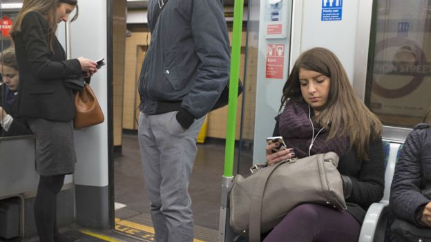 Commuters on mobiles