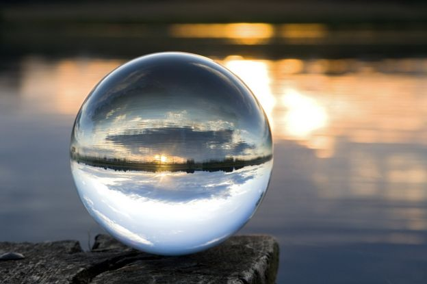 a crystal ball by a lake at sunset