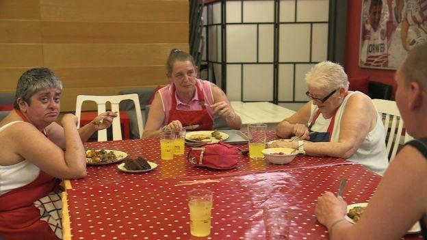 Mulheres sentadas à mesa se alimentando em uma da slanchonetes participants do projeto