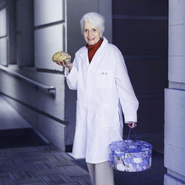 Marian Diamond con un cerebro en la mano y una caja para sombreros