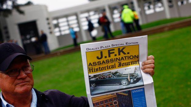 Turista segura jornal falando da morte de John Kennedy em frente à praça Dallas, nos EUA