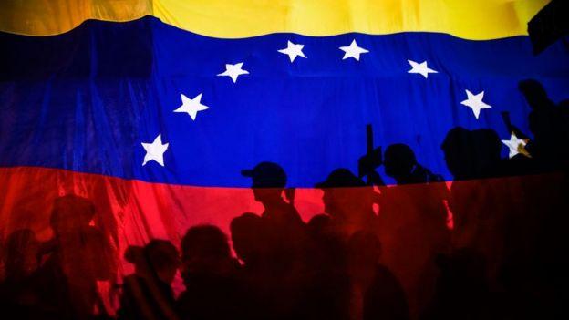 Bandera de Venezuela con personas protestando a contraluz.