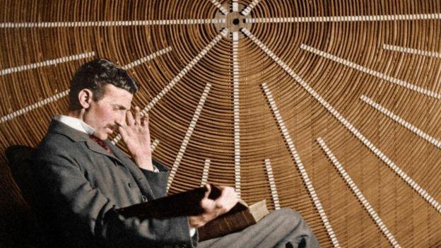 Nicola Tesla, sentado, leyendo un libro