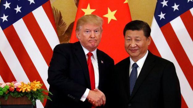 Donald Trump y Xi Jinping se saludan.