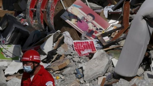 A photo of a child is seen among the ruins of a 17-storey apartment building that collapsed after an earthquake hit Tainan, southern Taiwan February 7, 2016