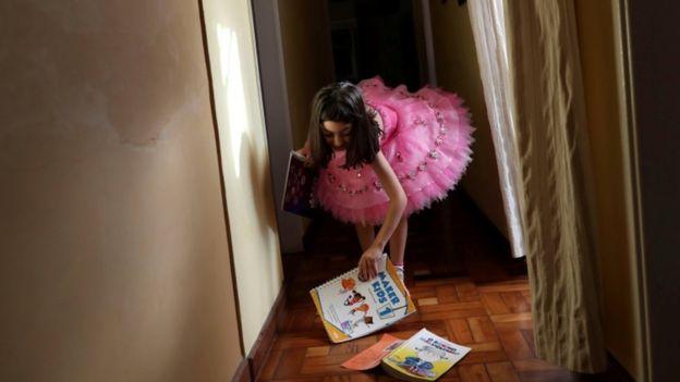 Menina de 5 anos com seus livros escolares e de literatura em Santo André (SP), em meio à quarentena