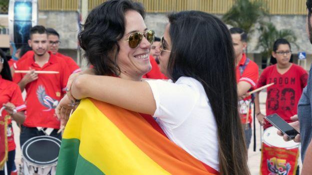 Una pareja de mujeres se abrazan envueltas en una bandera del orgullo gay fuera de la Corte Suprema en Costa Rica.
