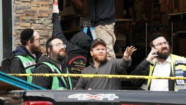 Miembros de la comunidad judía ortodoxa observan los destrozos ocurridos en el supermercado.