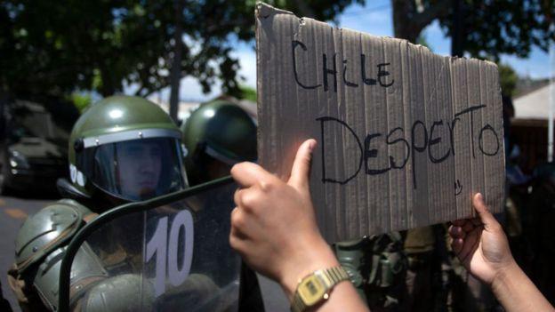 """""""Chile despertó"""", dice un cartel frente a los policías."""