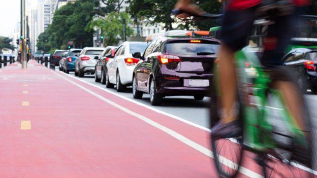 Mujere en bicicleta junto a una calle con tráfico.