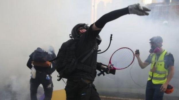 Demonstran melempar balik gas air mata ke arah petugas dalam protes di Hong Kong.