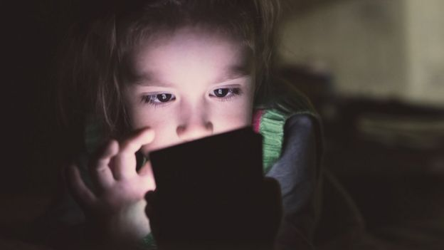 Girl watching a screen in the dark.
