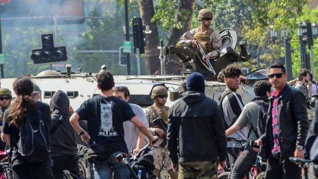 A soldier in a tank is surrounded by demonstrators in Santiago