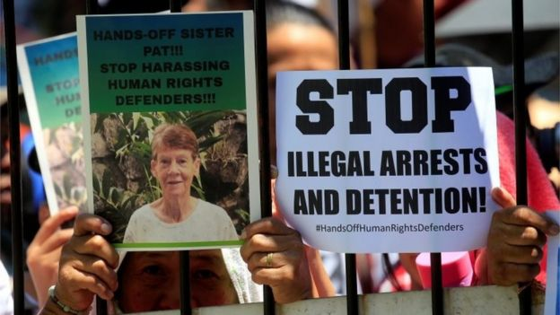Supporters of Australian nun Patricia Fox, 71, hold placards while waiting for her release outside of the Bureau of Immigration headquarters in Metro Manila, Philippines April 17, 2018.