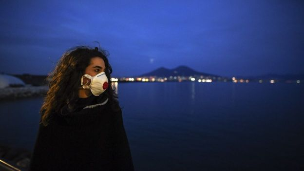 A woman wearing antivirus masks, to protect herself from the Coronavirus (Covid 19) waiting for a super moon walks at sunset on the Naples waterfront in front of the Vesuvius volcano.