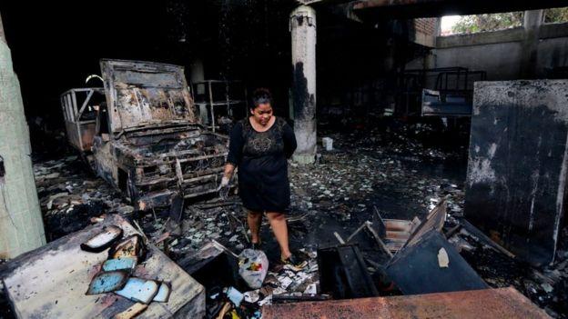 Una mujer observa los restos calcinados de la vivienda.