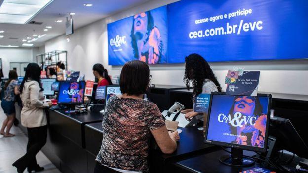 Imagem mostra funcionários e clientes em balcão de atendimento em uma loja da C&A no Brasil