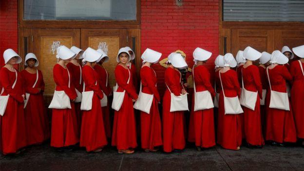 The Handmaid's Tale diziye de uyarlandı. Dizideki kadınların giydiği kıyafetleri giyen bir grup kadın, ABD'de sokakta yürürken